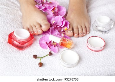 beauty composition - feet with acrylic toenails, flowers and crystals