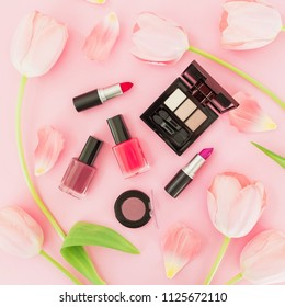 Beauty composition with tulips flowers and female cosmetics on pink background. Top view. Flat lay.