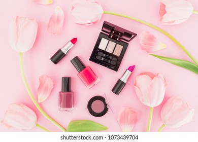 Beauty composition with tulips flowers and makeup cosmetics on pink background. Top view. Flat lay.
