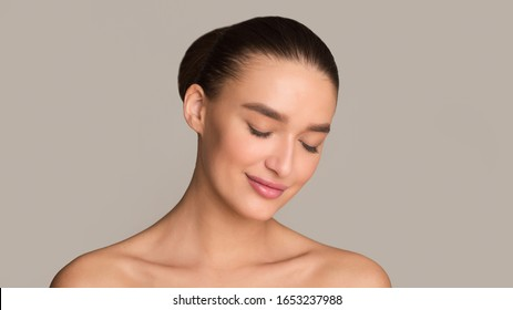 Beauty concept. Beautiful girl face with closed eyes, perfect skin and nude makeup, grey background