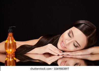 Beauty concept, brunette woman with closed eyes lying on black glass with her reflexion. Gorgeous model with hair oil near her, head and shoulders, beauty portrait