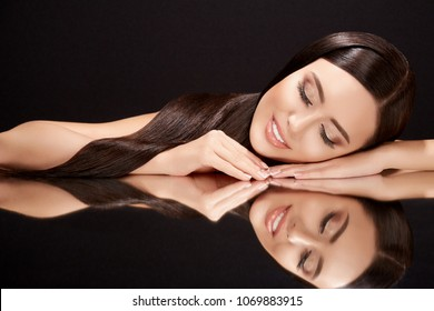 Beauty concept, brunette woman with closed eyes lying on black glass with her reflexion. Gorgeous model with natural makeup, head and shoulders, beauty portrait