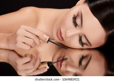 Beauty concept, brunette woman with closed eyes lying on black glass with her reflexion. Gorgeous model holding mascara, head and shoulders, beauty portrait, closeup