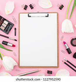 Beauty concept with clipboard, flowers, cosmetics and accessory on pink background. Top view. Flat lay. Feminine desk.