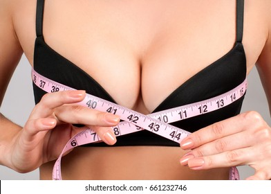 Beauty concept. Closeup of young woman measures her breast with a measuring tape