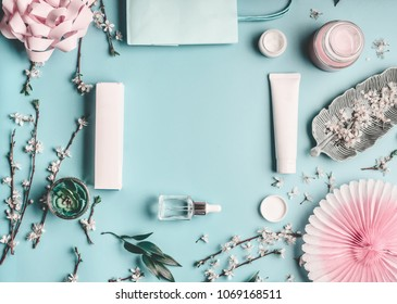 Beauty concept with facial cosmetic products, shopping bag and twigs with cherry blossom on pastel blue desktop background. Modern spring skin care trends, top view, frame, flat lay. Branding mock up