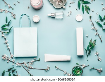 Beauty concept with facial cosmetic products, shopping bag and cherry blossom on pastel blue desktop background. Modern spring skin care layout, top view, frame, flat lay. Branding mock up