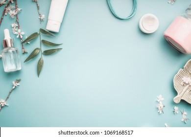 Beauty concept with facial cosmetic products, green leaves and cherry blossom on pastel blue desktop background. Modern skin care layout, top view, frame, flat lay. Branding mock up