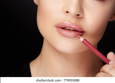 Beauty concept, half face of woman, only lips, lower part of face. Woman putting on makeup, painting lips with red lipliner. Closeup of lips touched with pencil, studio, black background