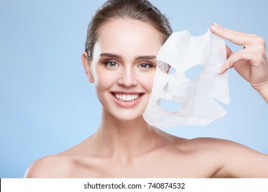 Beauty concept, head and shoulders of girl removing mask from face, face pack. Young woman with pure skin, looking at camera and smiling happily. Studio, grey background