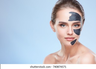 Beauty concept, head and shoulders of girl with grey mask on face, face pack. Young woman looking at camera. Studio, grey background, copyspace