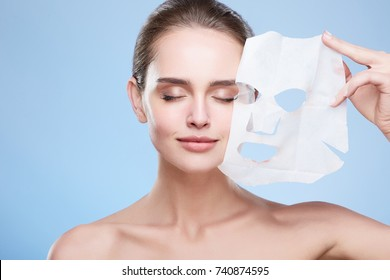 Beauty concept, head and shoulders of girl removing mask from face, face pack. Young woman with pure skin, closed eyes and smiling. Studio, grey background