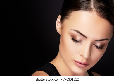 Beauty concept, head and shoulders portrait of beautiful model with nude make-up and closed eyes, closeup. Brunette woman bowing head in studio with black background, interior