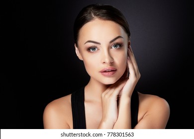 Beauty concept, head and shoulders portrait of beautiful model with nude make-up looking at camera, touching face. Brunette woman in studio with black background, interior