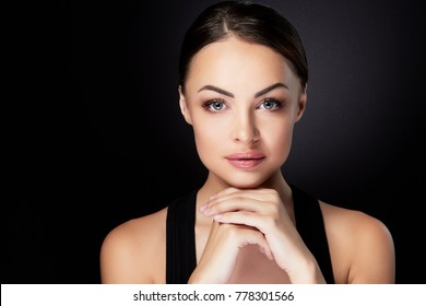 Beauty concept, head and shoulders portrait of beautiful model with nude make-up looking at camera, fingers together under chin. Brunette woman in studio with black background, interior
