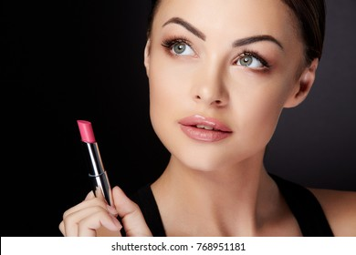 Beauty concept, head and shoulders of woman looking up and aside, holding rose lipstick. Beauty portrait of model with rose lips painted with lip gloss, studio with black background