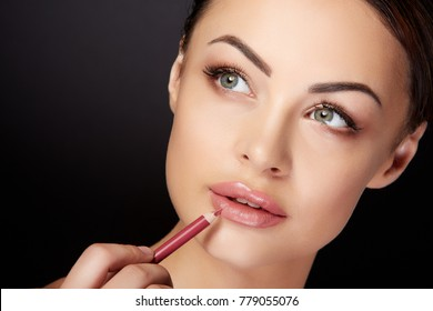 Beauty concept, head and shoulders of woman drawing contour on  lips with red lipliner. Portrait of woman touching lips with pencil and looking aside, studio, black background