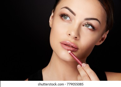 Beauty concept, head and shoulders of woman putting on makeup, painting lips with red lipliner. Portrait of woman touching lips with pencil and looking aside, studio, black background