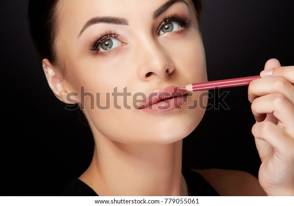 Beauty concept, head and shoulders of woman drawing contour on  lips with red lipliner. Portrait of woman touching lips with pencil and looking up, studio, black background