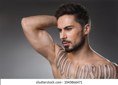 Beauty concept. Pensive man with strong muscularity holding hand on back of his hand. Isolated on background