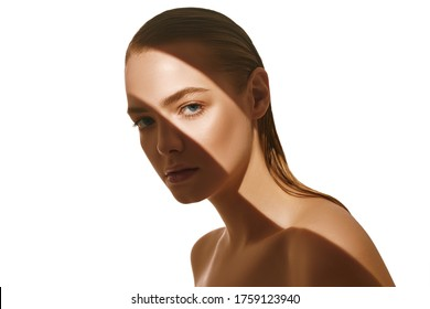 Beauty concept. Portrait of a beautiful young woman with fresh natural make-up and perfect healthy skin. The play of light and shadow. Fashion. Copy space.