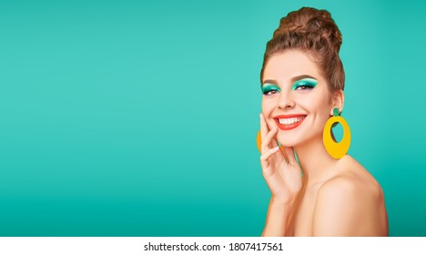 Beauty concept. Portrait of a cheerful young woman with colorful makeup and beautiful smile posing on a vivid background. Makeup and cosmetics. Studio shot. Copy space.