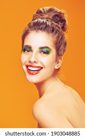 Beauty concept. Portrait of a cheerful young woman with bright colorful makeup and beautiful smile posing on a yellow background. Makeup and cosmetics. Studio shot.
