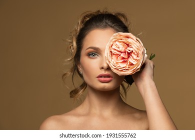 beauty concept portrait , of a fashion model posing on beige background , with a big flower rose on one eyes. spring concept