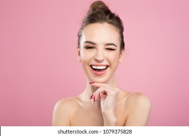 Beauty concept. Portrait of playful attractive woman is posing naked while looking at camera with smile. She is touching her chin with wide smile. Isolated on pink background