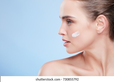 Beauty concept, beauty portrait of young woman with cream on cheek. Profile of naturally beautiful woman looking aside, studio, inside. Cream on cheek, cosmetology