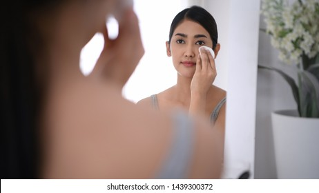 Beauty concept. Reflections on Asian women wiping makeup in the mirror.