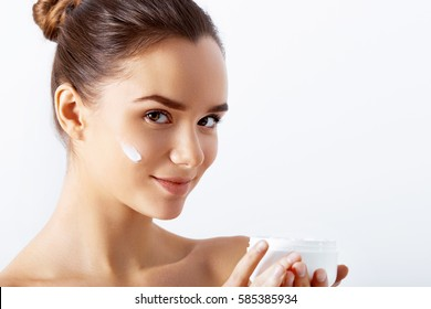 Beauty Concept. Taking good care of her skin. Attractive young woman looking at camera and smiling while standing against background