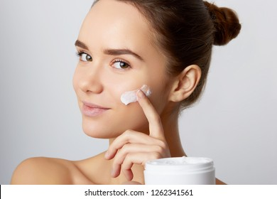Beauty Concept. woman holds a moisturizer in her hand and spreads it on her face  to moisturize her skin and wrinkle from impurities. body care, skincare.Taking good care of her skin