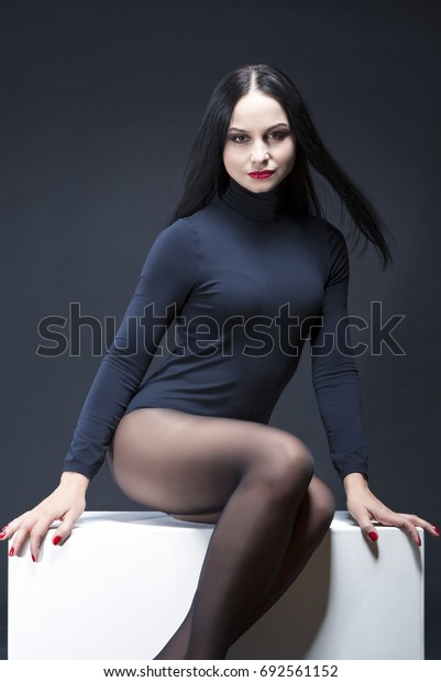 Beauty Concepts and Ideas. Natural Studio Portrait of Mid Aged Sexy Sensual Caucasian Brunette Woman Posing in Black Body Suit.Vertical Image Composition