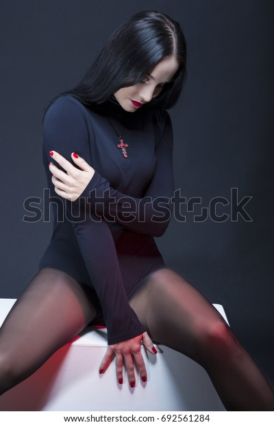 Beauty Concepts. Studio Portrait of Mid Aged Sexy Relaxed Caucasian Brunette Woman Posing in Black Body Suit with Symbolyc Cross Necklace. Sitting on White Box. Vertical Image Composition