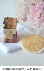 Beauty and cosmetic business - handmade natural soap bars with loofah, pink peony flowers and glass vials with facial toners and massage loofah