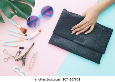 Beauty and cosmetic items, fashion sunglasses and woman hand holding clutch bag on pastel color background