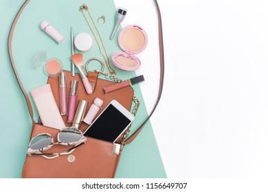 Beauty and cosmetic products spilling out of a woman's handbag.