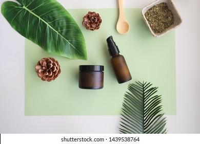 Schöne kosmetische Hautpflege auf grünem Hintergrund.Produkte mit Blume, Blätter auf dem Tisch Draufsicht, flach.minimale moderne