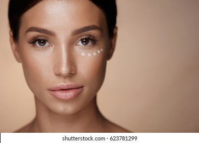 Beauty Cosmetics. Closeup Of Attractive Young Woman With Concealer Under Eyes. Portrait Of Beautiful Sexy Female Model With Fresh Clean Skin And Natural Makeup. Facial Make-up. High Resolution