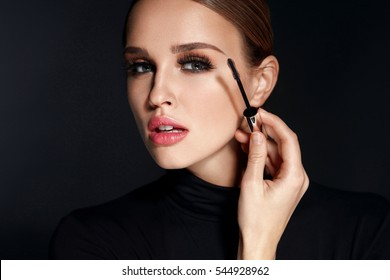 Beauty Cosmetics. Closeup Of Beautiful Sexy Woman Putting Black Mascara On Long Thick Eyelashes With Brush. Fashionable Female Model With Soft Skin, Perfect Makeup And Fake Eyelashes. High Resolution