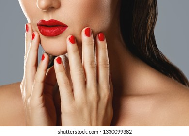 Beauty and cosmetics. Close-up of female mouth and nails with red manicure and lipstick.