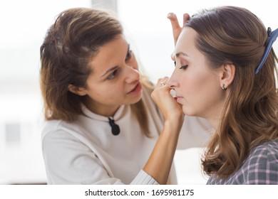 Concepto de belleza y cosmética - Artista maquillador que hace maquillaje profesional de mujer joven