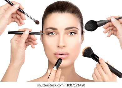 Beauty and cosmetics concept with makeup brushes held in the hands of female beauticians surrounding the face of a beautiful young brunette woman isolated on white. Makeup process