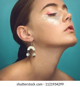 Beauty, cosmetics and makeup. Close up shot of beautiful woman's face with perfect art make up with glitter.