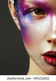 Beauty, cosmetics and makeup. Magic eyes look with bright creative make-up. Macro shot of beautiful woman's face with perfect art make up with glitter. Body art