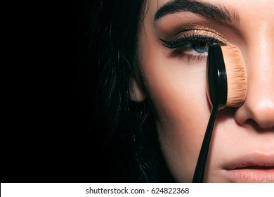 beauty and cosmetics, pretty woman or cute sexy girl with brunette hair, has long eyelashes, fashionable eye makeup on adorable face holds foundation make up brush near face on black background.