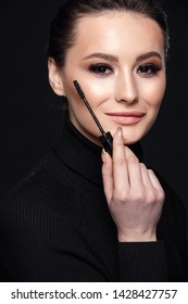 Beauty Cosmetics.Woman applying black mascara on eyelashes with makeup brush. photos of appealing brunette girl on black background.High Resolution
