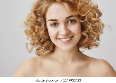 Beauty and cosmetology concept. Close-up portrait of attractive curly haired woman with bright kind smile standing naked over gray background, posing for advertising near copy space