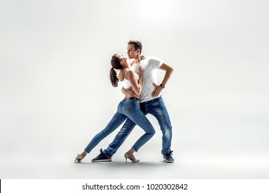 beauty couple dancing social danse ( kizomba or bachata or semba or taraxia) , on light grey background
